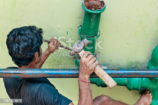 Kolkata, 08/16/2020: An Indian building construction worker, holding  a metallic construction frame, trying to replace a rusty metal pipe on a building wall.