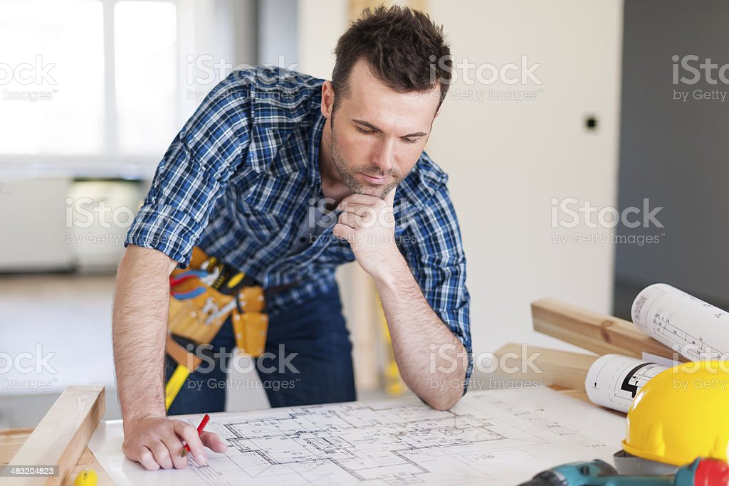 Building contractor bending over home plans stock photo