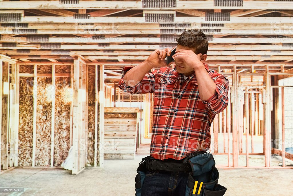 Building contractor on phone in contraction...