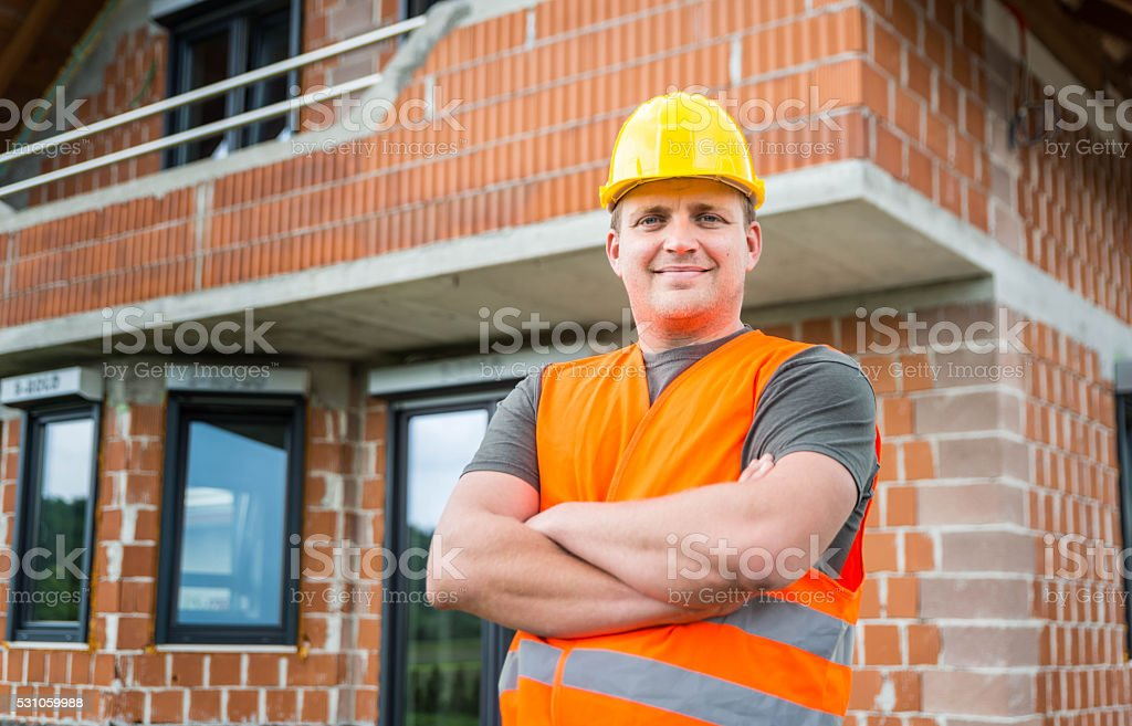 Building Contractor in front of a new house in build