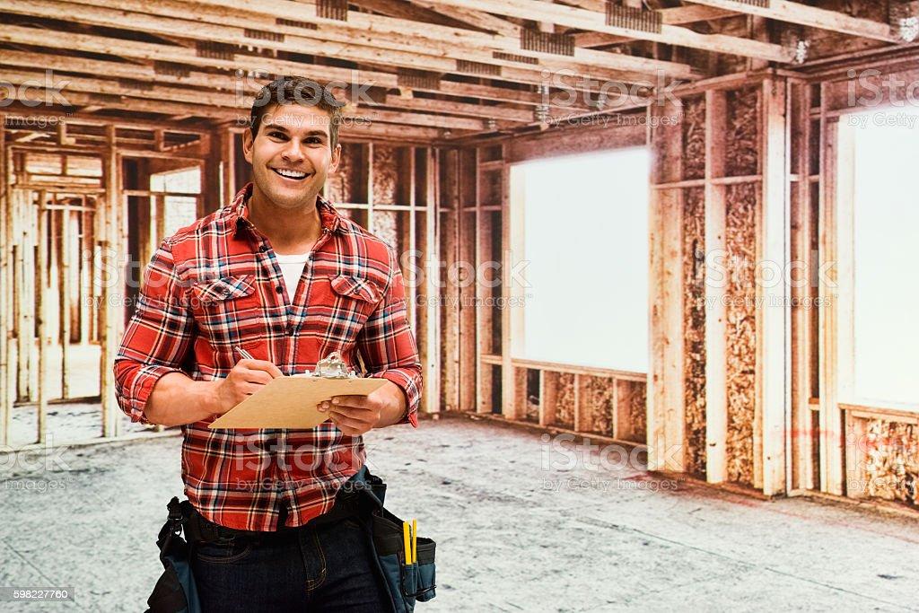 Empreiteira de pé em construção local foto royalty-free