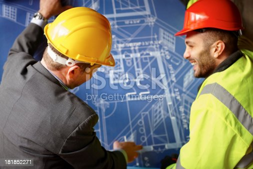 istock Building contractors reviewing blueprints on construction site 181852271