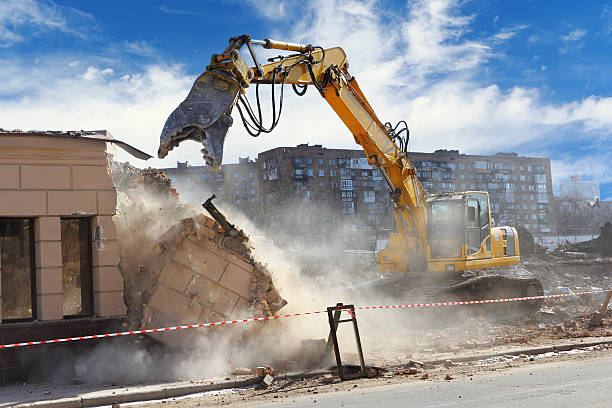 Building demolition machine pulls down a wall on a sunny day Bulldozer crushing the building at construction site demolishing stock pictures, royalty-free photos & images