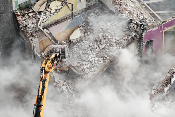 Building demolition with an excavator in dust cloud. Building demolition with an excavator in dust cloud, view from above. demolishing stock pictures, royalty-free photos & images