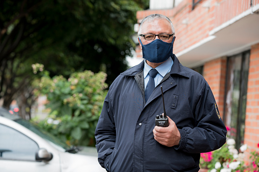 The doorman of the building is a Latino from Bogota Colombia, between 50 and 59 years of age, looking at the camera in a portrait while wearing his mask to avoid the Covid 19 and holding his radio