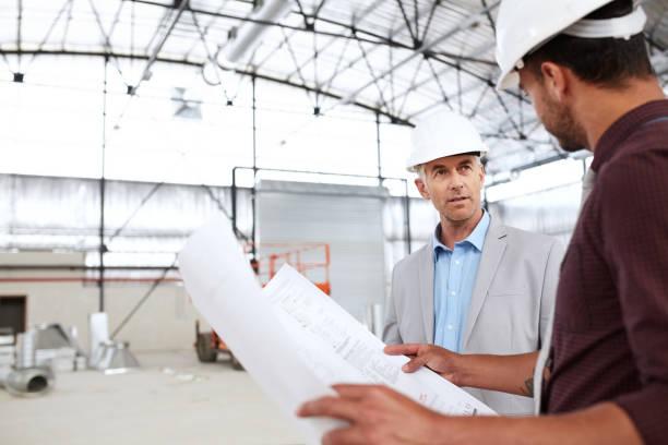 Bauingenieure im Gespräch über Baupläne während einer Baustelleninspektion – Foto
