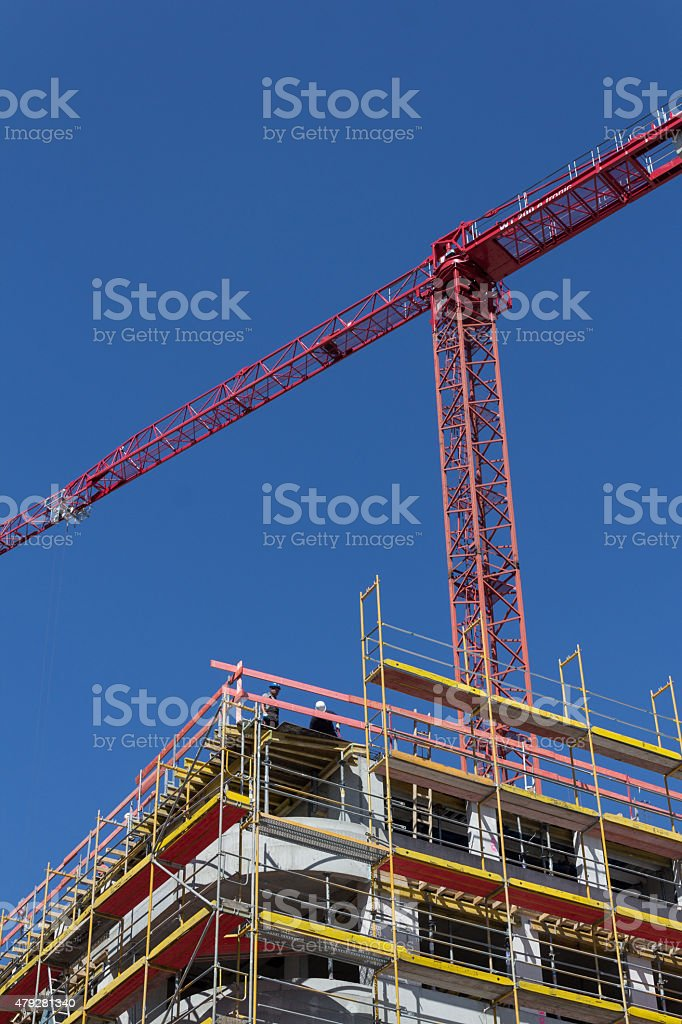 building facade with scaffolding and crane - construction site stock photo