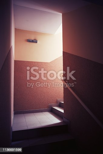 On staircases in a building hall, dark and moody atmosphere.