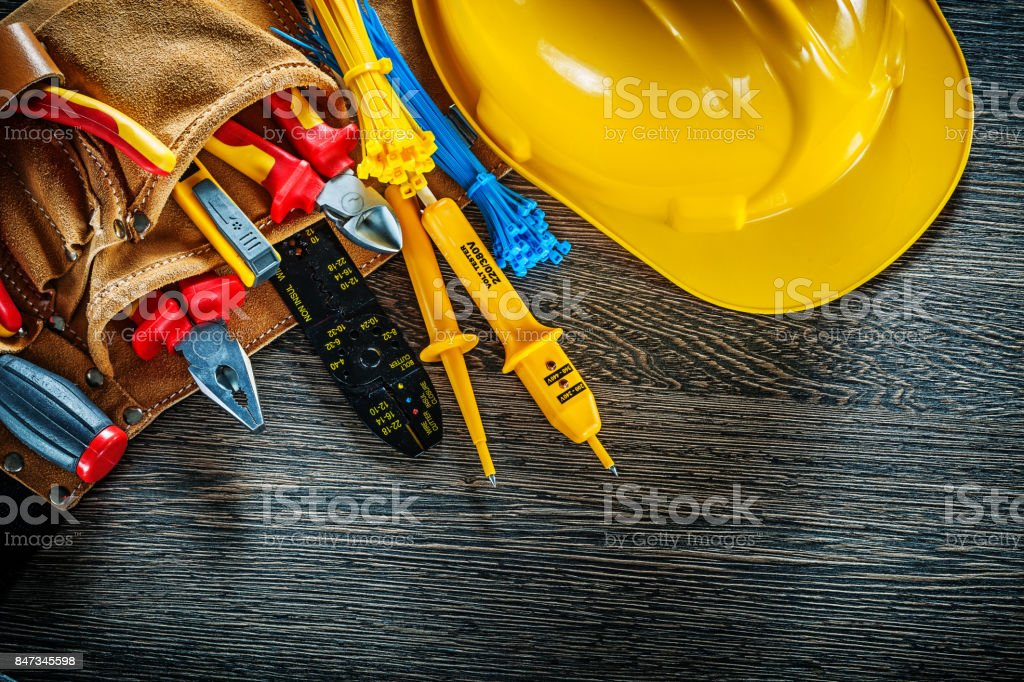 Building helmet leather construction belt on wooden board electr stock photo