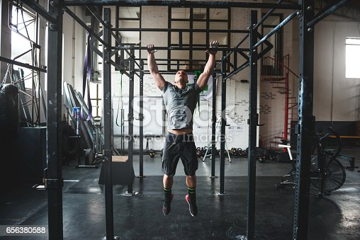 Handsome man doing pull ups in the gym.