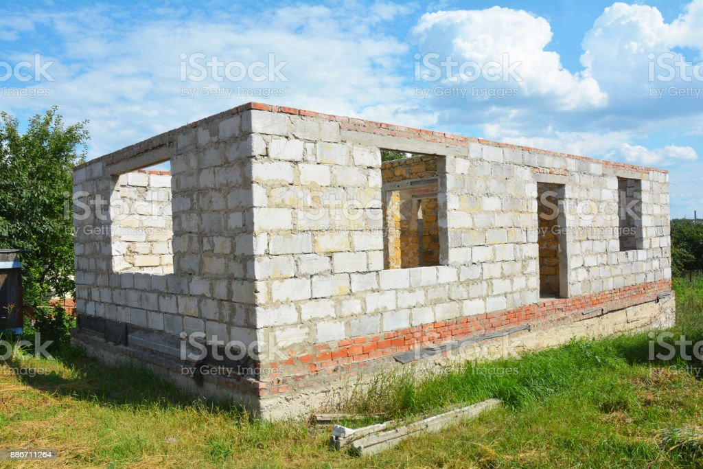Building House from Autoclaved Aerated Concrete Blocks with concrete lintel and Unfinished Roof. stock photo