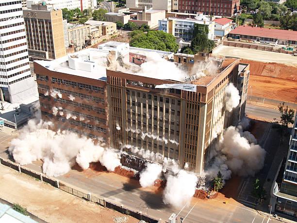 bâtiment implosion dans le centre-ville de johannesburg, afrique du sud + 2 - imploser photos et images de collection
