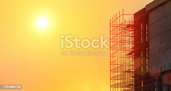 building in construction at sunset with scaffolding on the side
