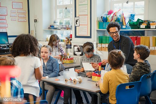 Elementary school children build 3d models using recycled materials with their teacher during class. This is a school in Hexham, Northumberland in north eastern England.