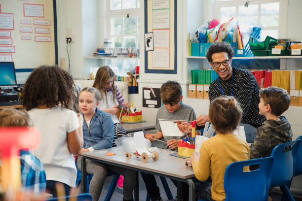 Building in Elementary Class with their Teacher Elementary school children build 3d models using recycled materials with their teacher during class. This is a school in Hexham, Northumberland in north eastern England. elementary age stock pictures, royalty-free photos & images