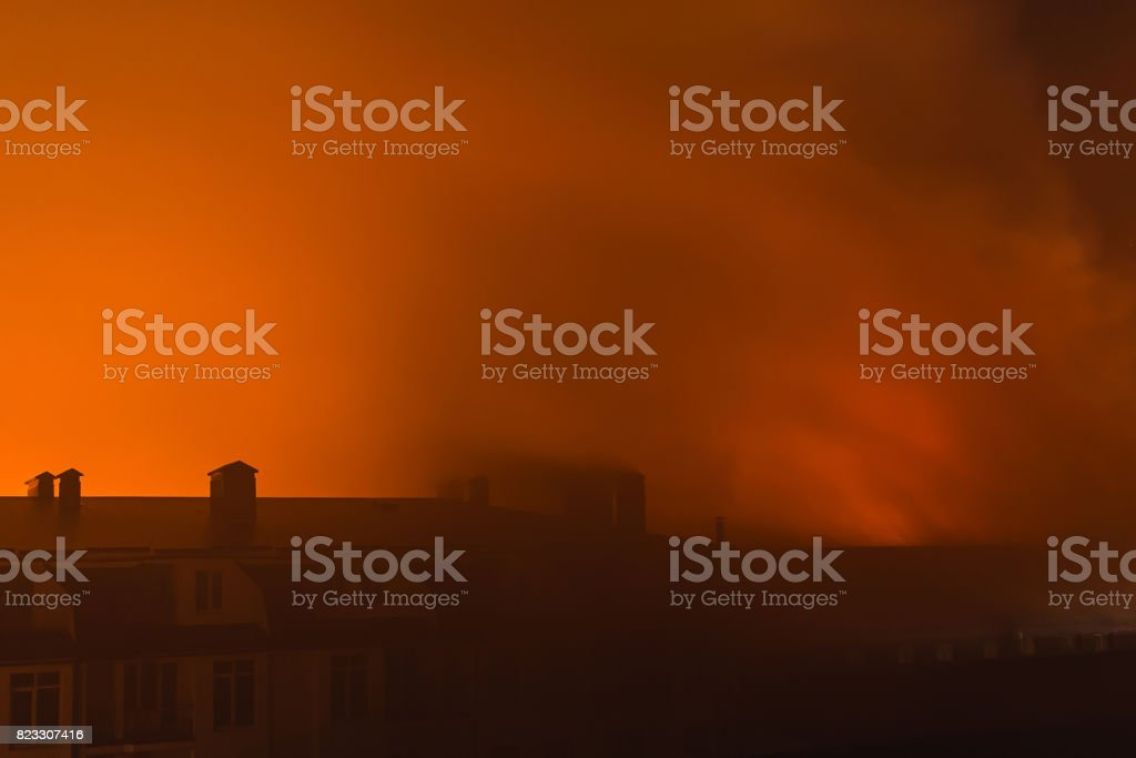 Building in fire at the night , burning fire flame with smoke on the...