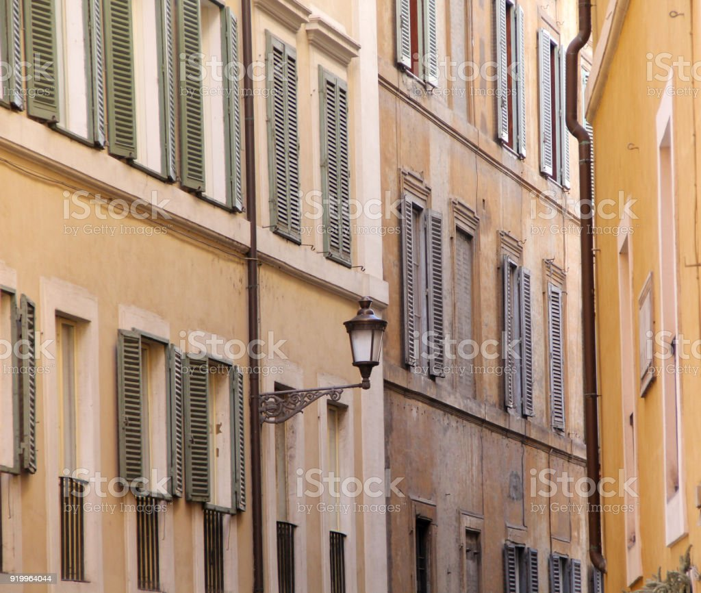 Building in Rome, details of old facade, wall with windows and wooden shutters. stock photo