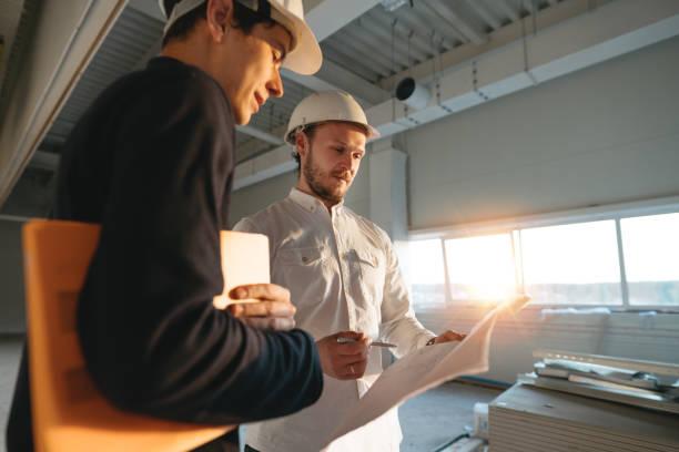 Bauindustrie. Junger Ingenieur im Gespräch mit Bauarbeiter auf der Baustelle. Industrieingenieure haben Treffen, während verwendet Blaupause – Foto
