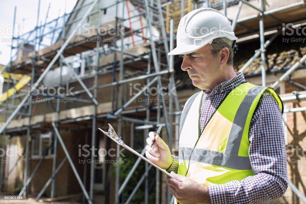 Building Inspector Looking At House Renovation Project stock photo