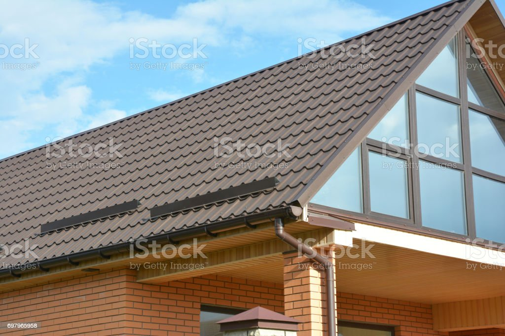 Building Modern House Construction with metal roof, rain gutter system and roof protection from snow, snow bar (Snow guard). Roof Snow Guards: Building Materials & Supplies. Attic skylight window. stock photo