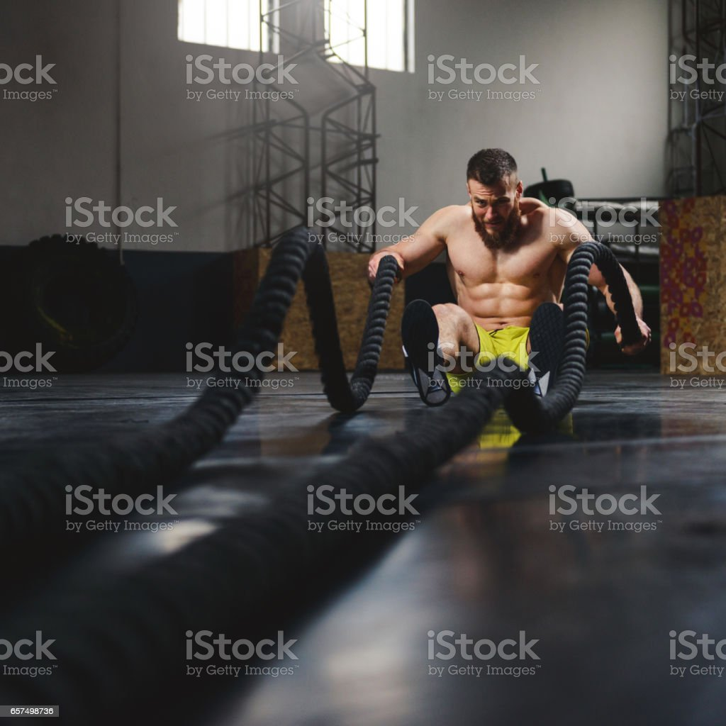 Building muscles with battle ropes stock photo