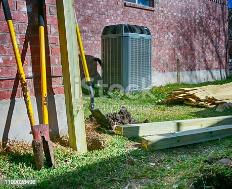 Backyard with modern air conditioner, shovels and lumber for new privacy fence.