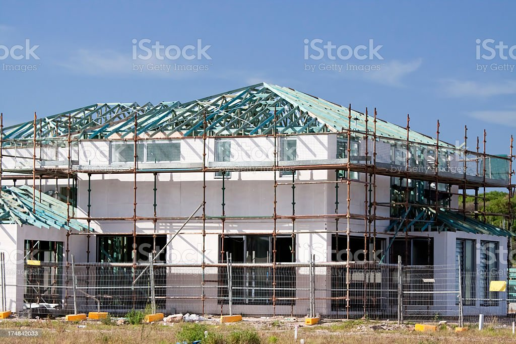 Building new house with scafolding and wooden roof trusses royalty-free stock photo