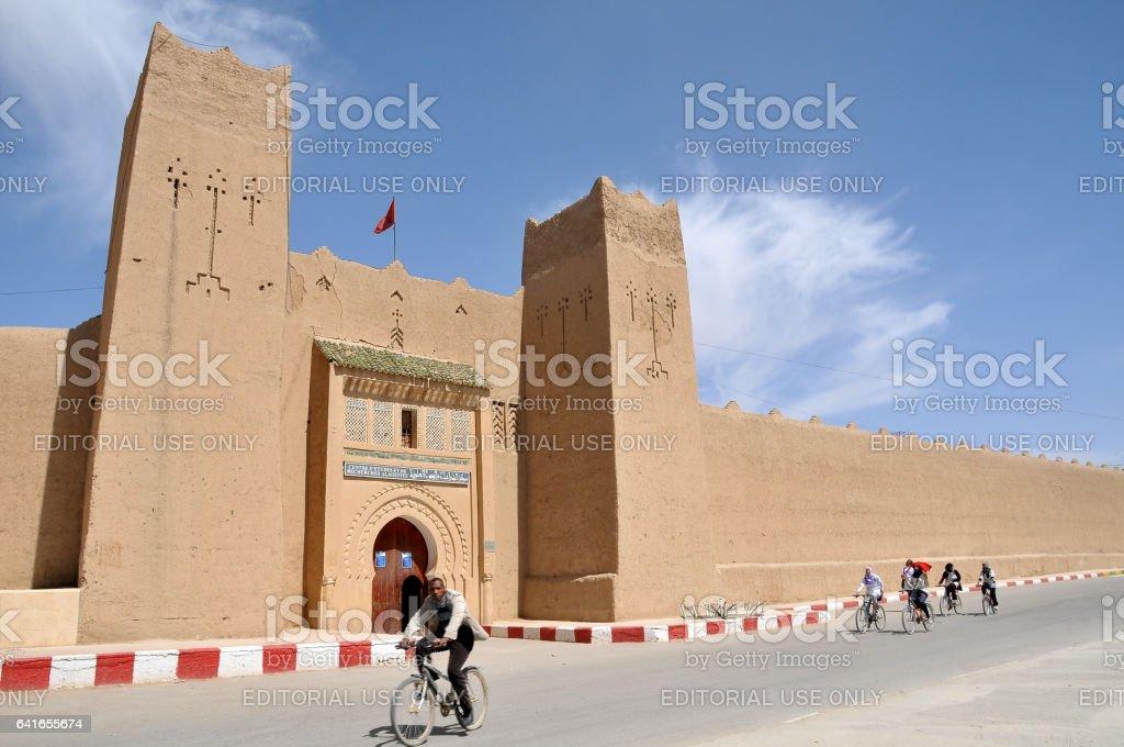 Edificio de barro y los ciclistas de Rissani - foto de stock