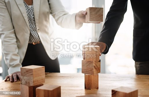 Shot of two unrecognizable businesspeople stacking wooden blocks together in an office