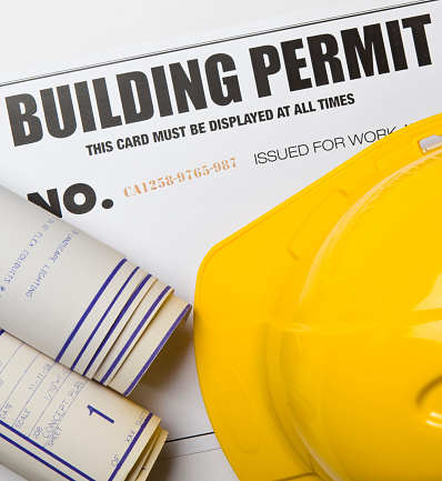 Building permit with hardhat and blueprints. Certificate was created by photographer with a graphics program. Code number is fictitious.