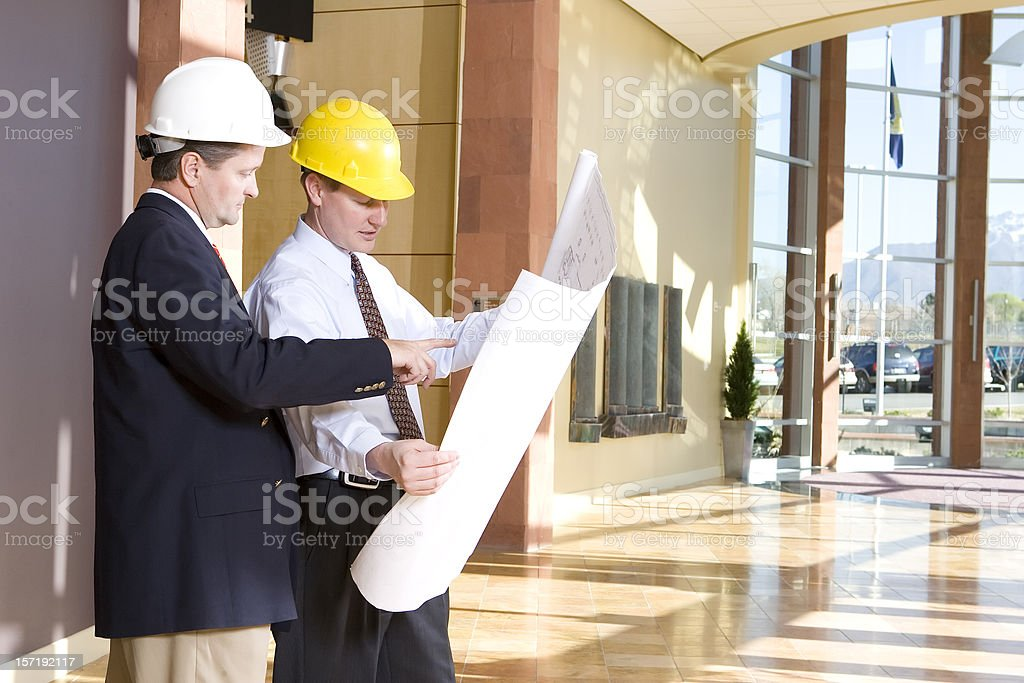 Building Planners Reviewing Blueprints royalty-free stock photo