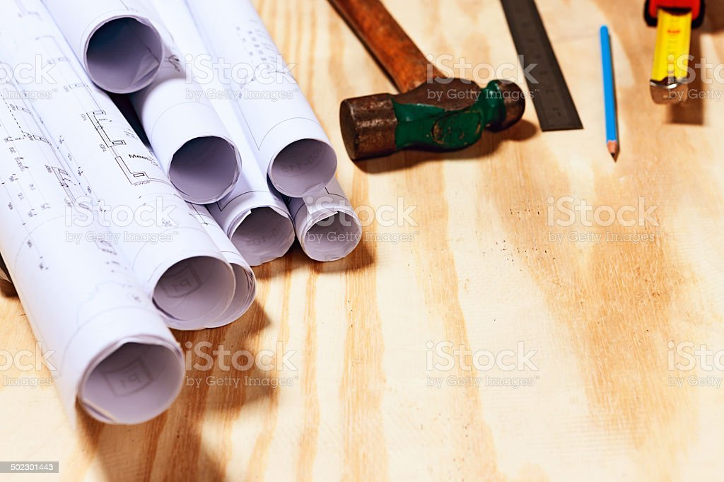 Building plans and variety of tools on wooden surface royalty-free stock photo