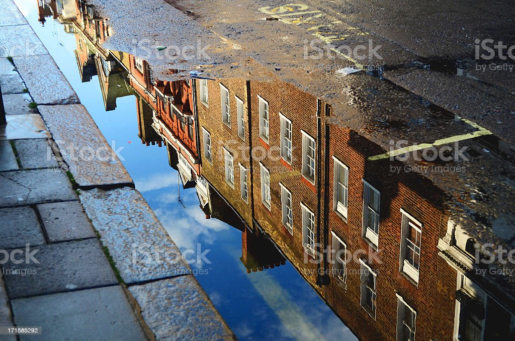 building reflected in roadside puddle stock photo