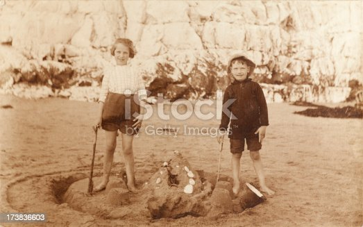 Vintage sepia photograph of a young boy and girl making a sandcastle at the beach in front of a cliff face. Some dust and scratches that reflect age of image.