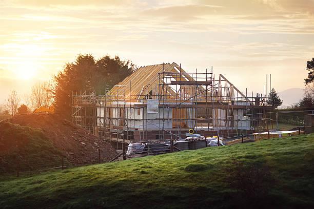 cantiere con casa in costruzione - costruire foto e immagini stock