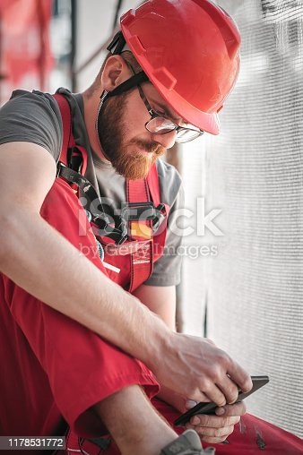 1054724700istockphoto Building site worker on the scaffolding using mobile phone 1178531772