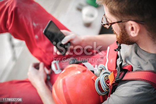 1054724700istockphoto Building site worker on the scaffolding using mobile phone 1178532706