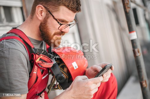 istock Building site worker on the scaffolding using mobile phone 1180447585