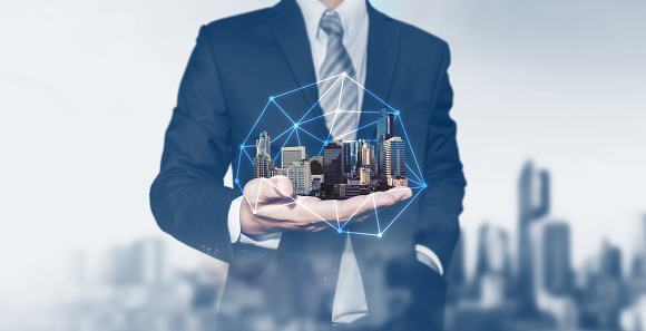 istock Building technology and business real estate investment. Businessman holding buildings on hand 982363998