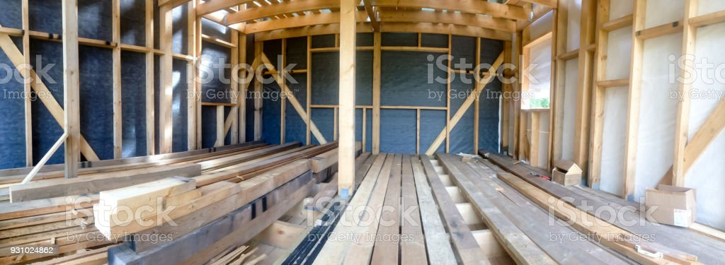 Building the frame of a wooden house. Panoramic picture inside the frame. Boards for flooring, vapor barrier walls. stock photo