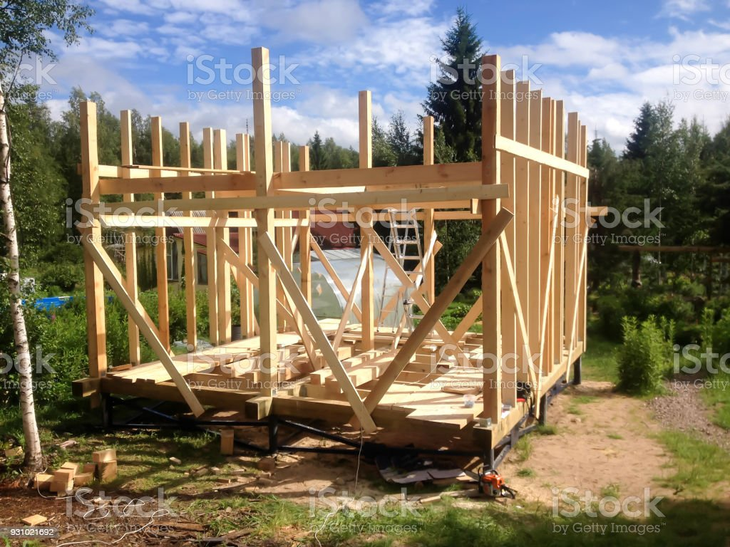 Building The Frame Of A Wooden House. Stage Of The Erection Of The Wall  Frame