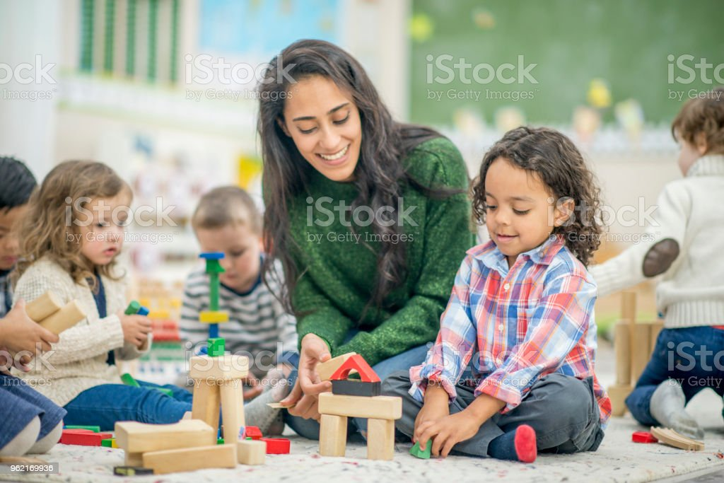 Building Together A boy and his teacher are indoors in their kindergarten classroom. They are building with blocks together. 25-29 Years Stock Photo