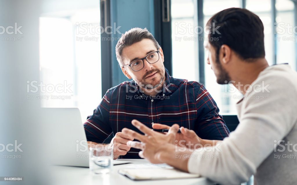 Building up on their ideas Shot of two businessmen having a discussion in an office Adult Stock Photo