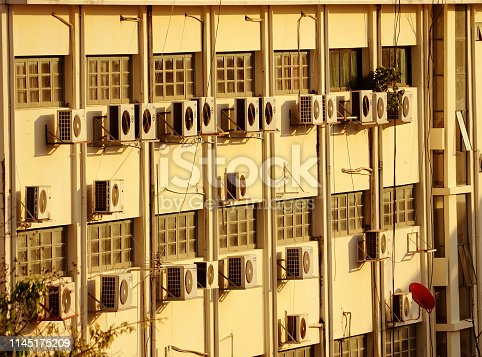 939450782 istock photo building wall with many air conditioners and red satellite dishes 1145175209
