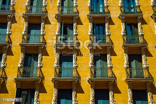 Old building with colorful facade and windows with iron balustrade, in a sunny day at Madrid. Capital of Spain this charming metropolis has vibrant and intense cultural life. Retouched photo.