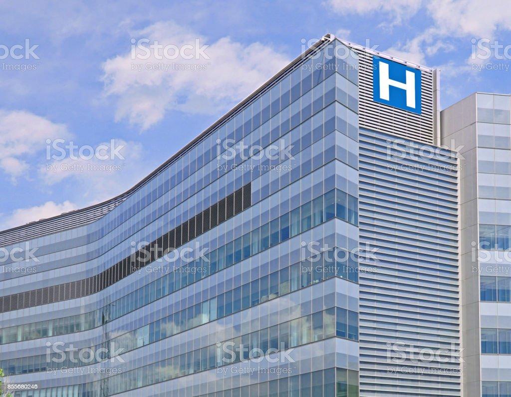 Edificio con gran cartel de H para el hospital - foto de stock