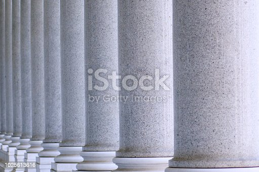 White columns on the facade of the building. Building with many columns