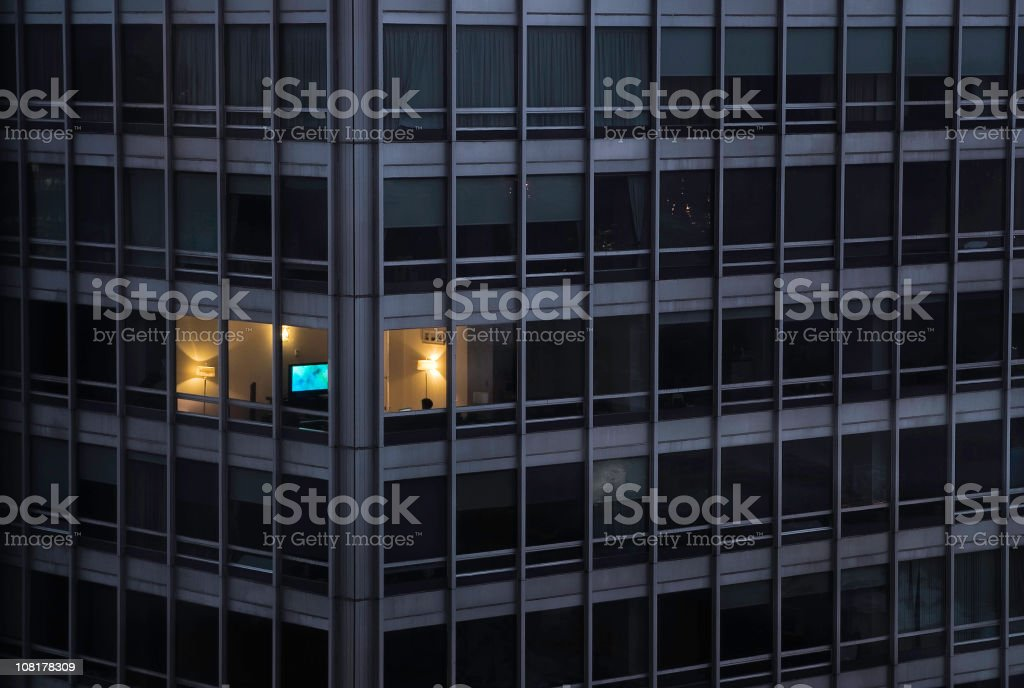 A building with only one light on stock photo
