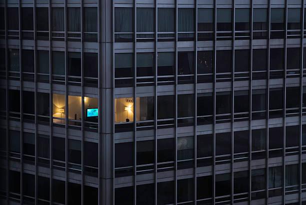a building with only one light on - fönsterrad bildbanksfoton och bilder