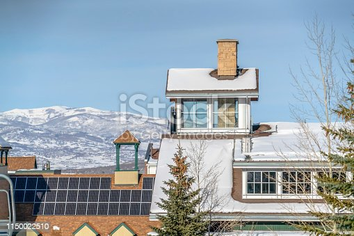 Building with solar panels and snow on the roof. Roof of a building with solar panels and snow in winter. A snow covered mountain and blue sky can be seen in the background in Park City, Utah.